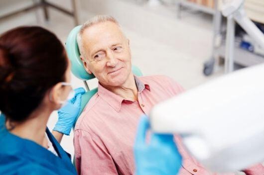 An older man sat at the dentist