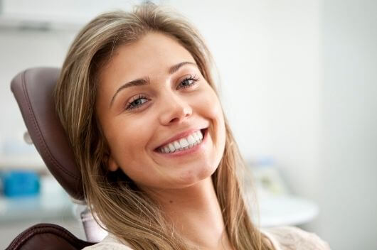 A woman smiling whilst sat in a dentist chair